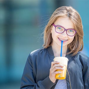 preteen girl with braces holding drink